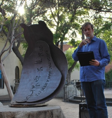 "Robert Peake reads a poem next to ""Elliot"" the bear"