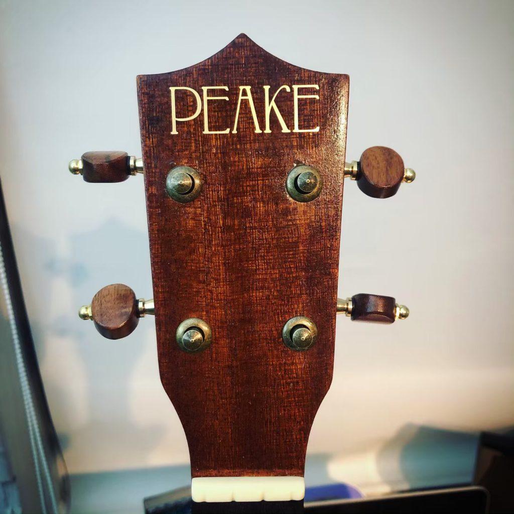 Image of ukulele head with the Peake logo on it