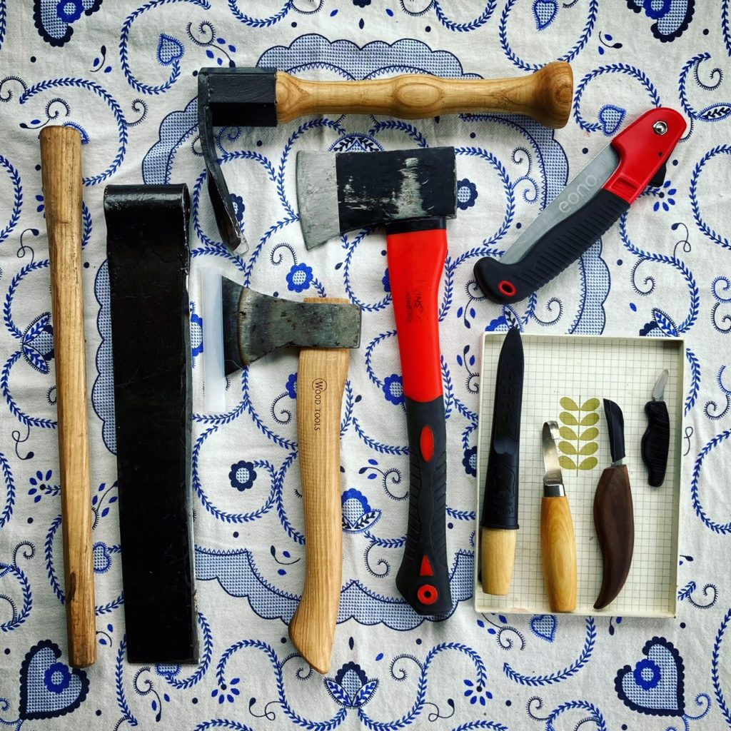 Image of various tools including carving knives, an axe, adze, and froe